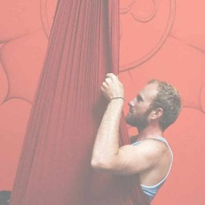 male smiling in aerial yoga hammock