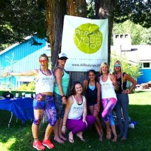 aireal yoga volunteers at wanderlust posing near a tree