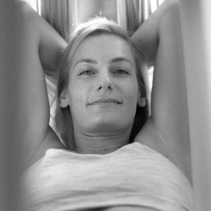 carmen curtis smiling in aireal yoga hammock