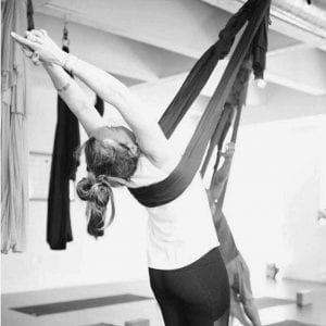 black and white woman doing prayer pose in aireal yoga hammock