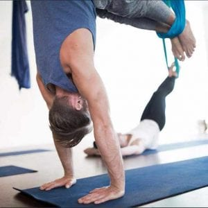 male doing handstand in aerial yoga apparatus
