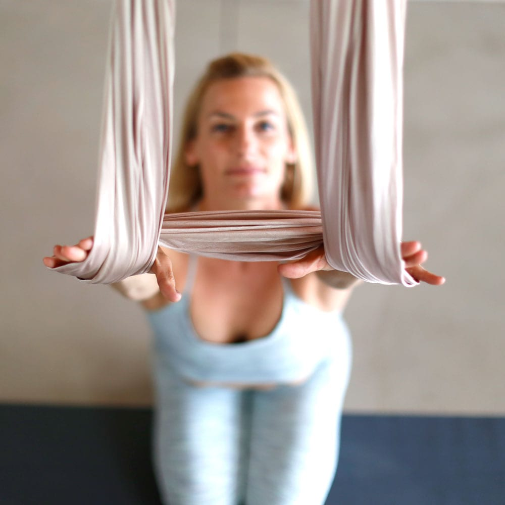 Yogis at certified AIReal Yoga studio doing half split in aerial yoga hammocks.