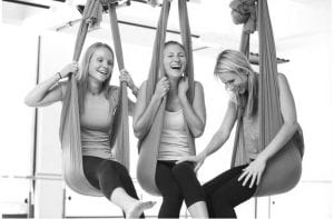 three girls laughing in aireal yoga hammock in colorado