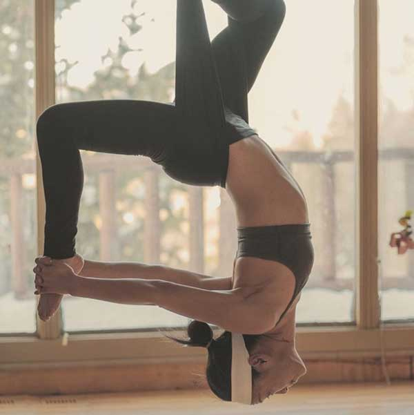 reverse dancer pose in aerial yoga with woman wearing heandband