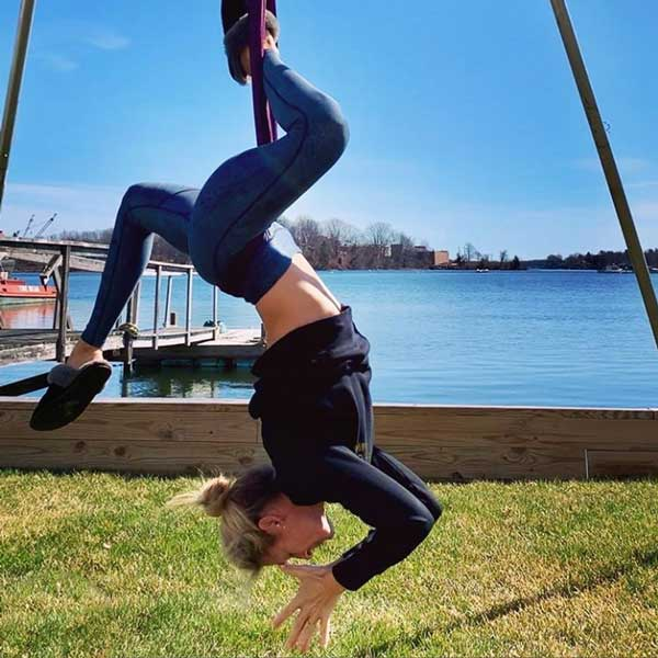woman on outdoor aerial yoga rig doing pigeon pose