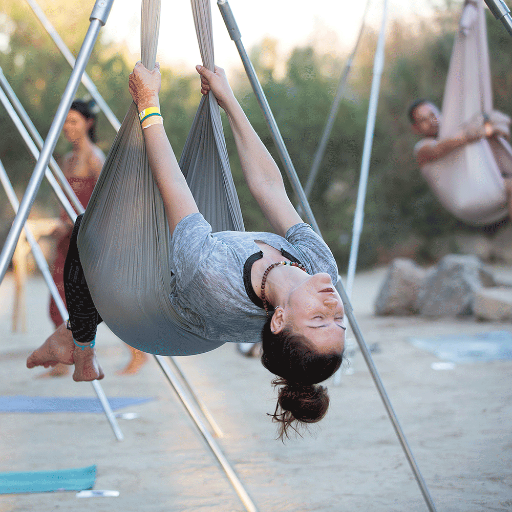 Woman relaxing in AIReal yoga pose at a Wanderlust Festival.